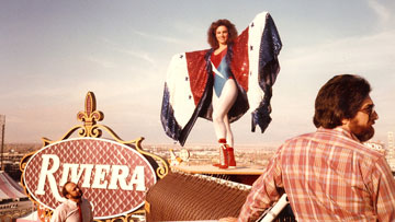 An image from Glow showing a female wrestler posing on a rooftop