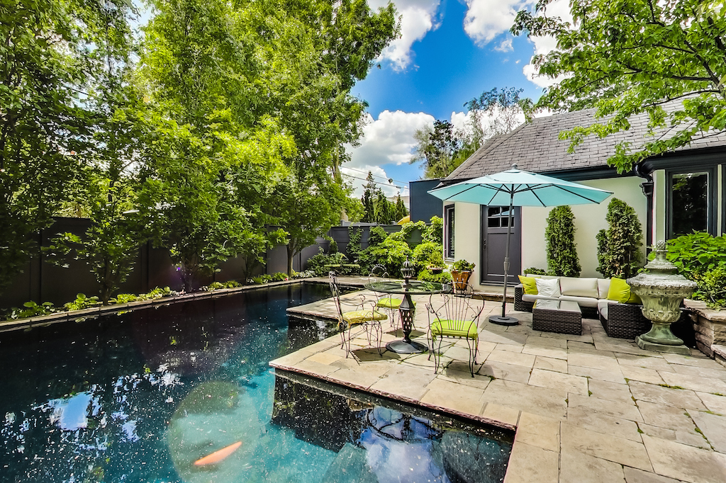The backyard has cottage-vibes thanks to plenty of aged greenery surrounding the area. The large patio space, inground pool and pool house look great for entertaining.