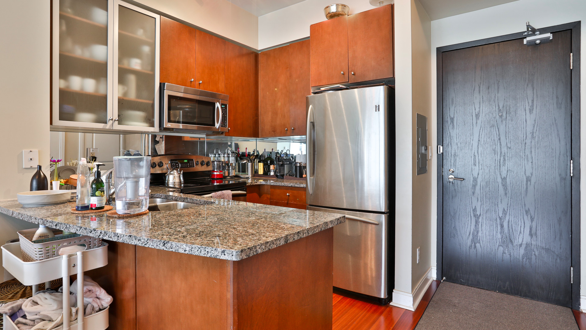 A photo of the kitchen area with granite countertops.