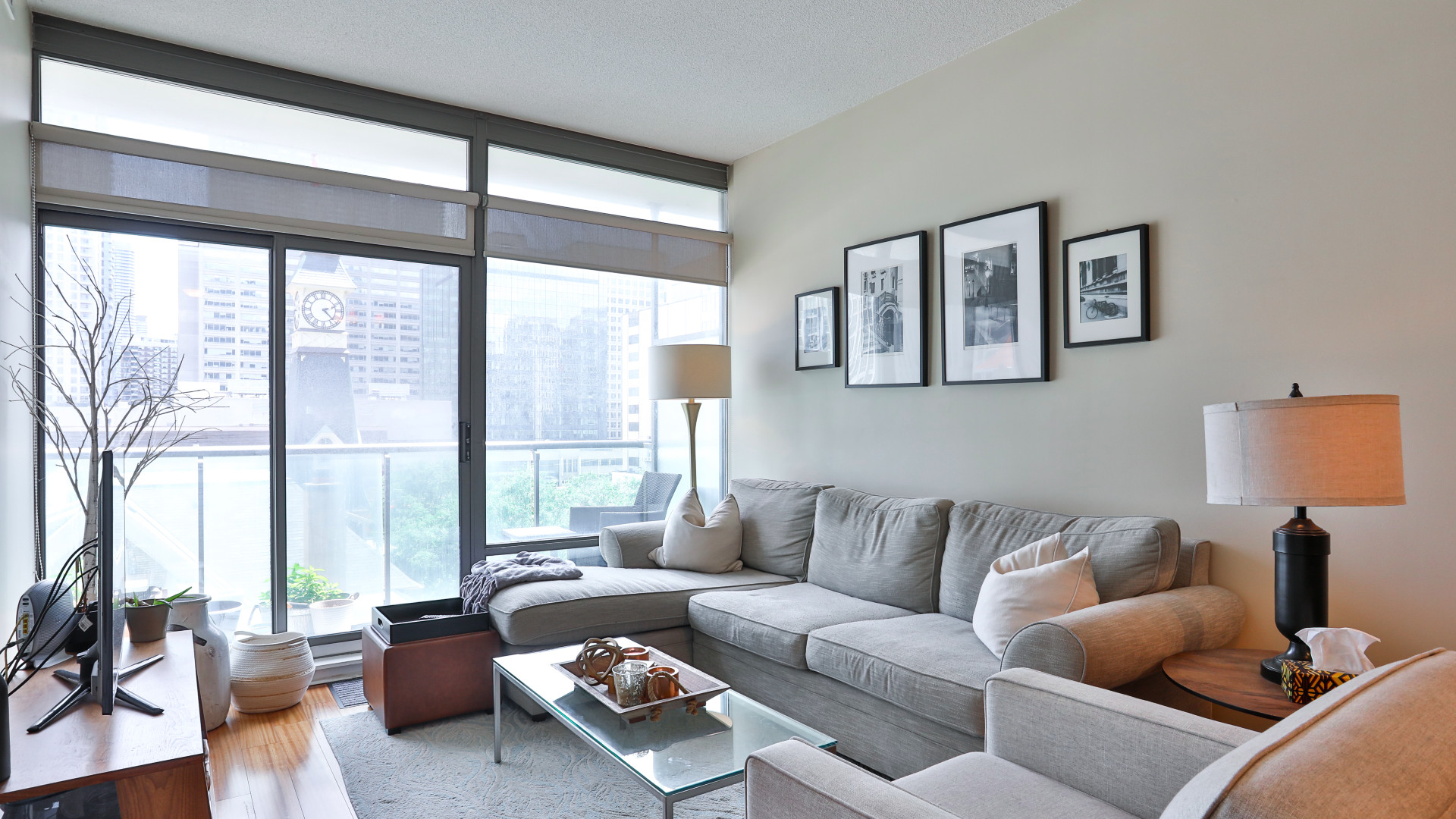 A photo of the living room and floor-to-ceiling windows.