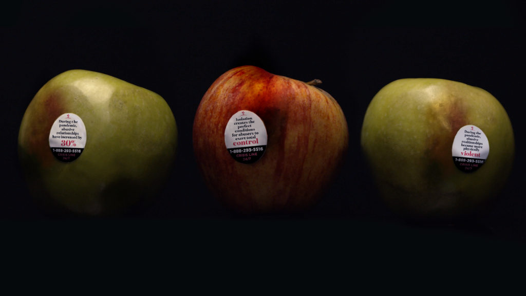 A photo of three apples with stickers explaining statistics about domestic violence.