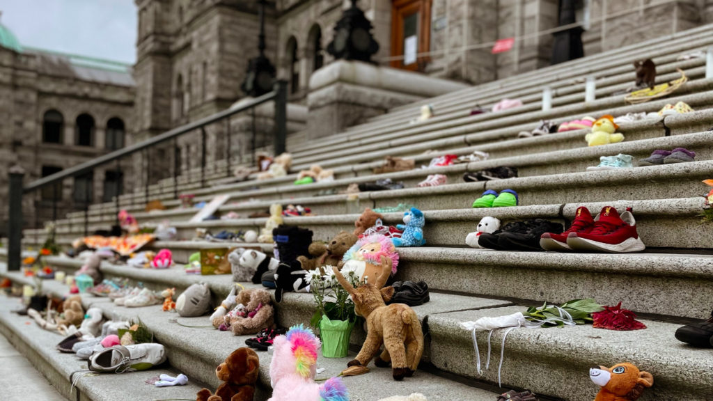 A photo of stuffed animals, shoes and other items left to honour the Indigenous children found in unmarked graves.