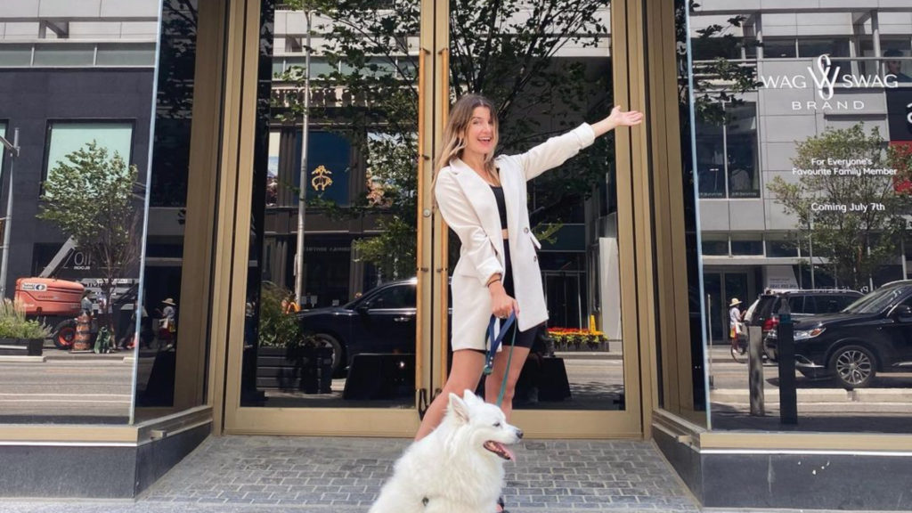 A photo of a person posed with their dog in front of the Wag Sawg boutique storefront on Bloor.