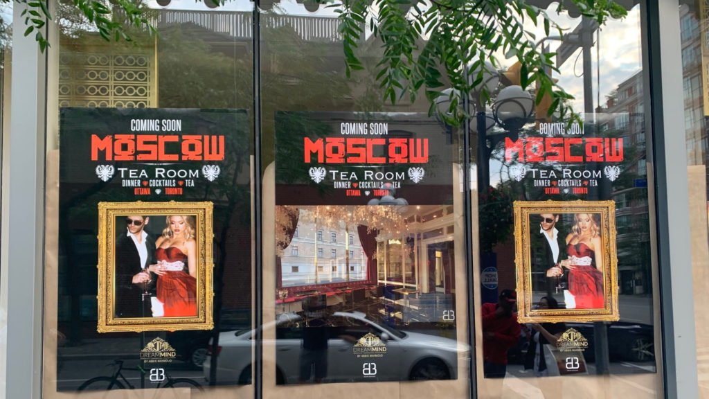 A photo of three Moscow Tea Room signs pasted along the front window of 161 Yorkville Ave.